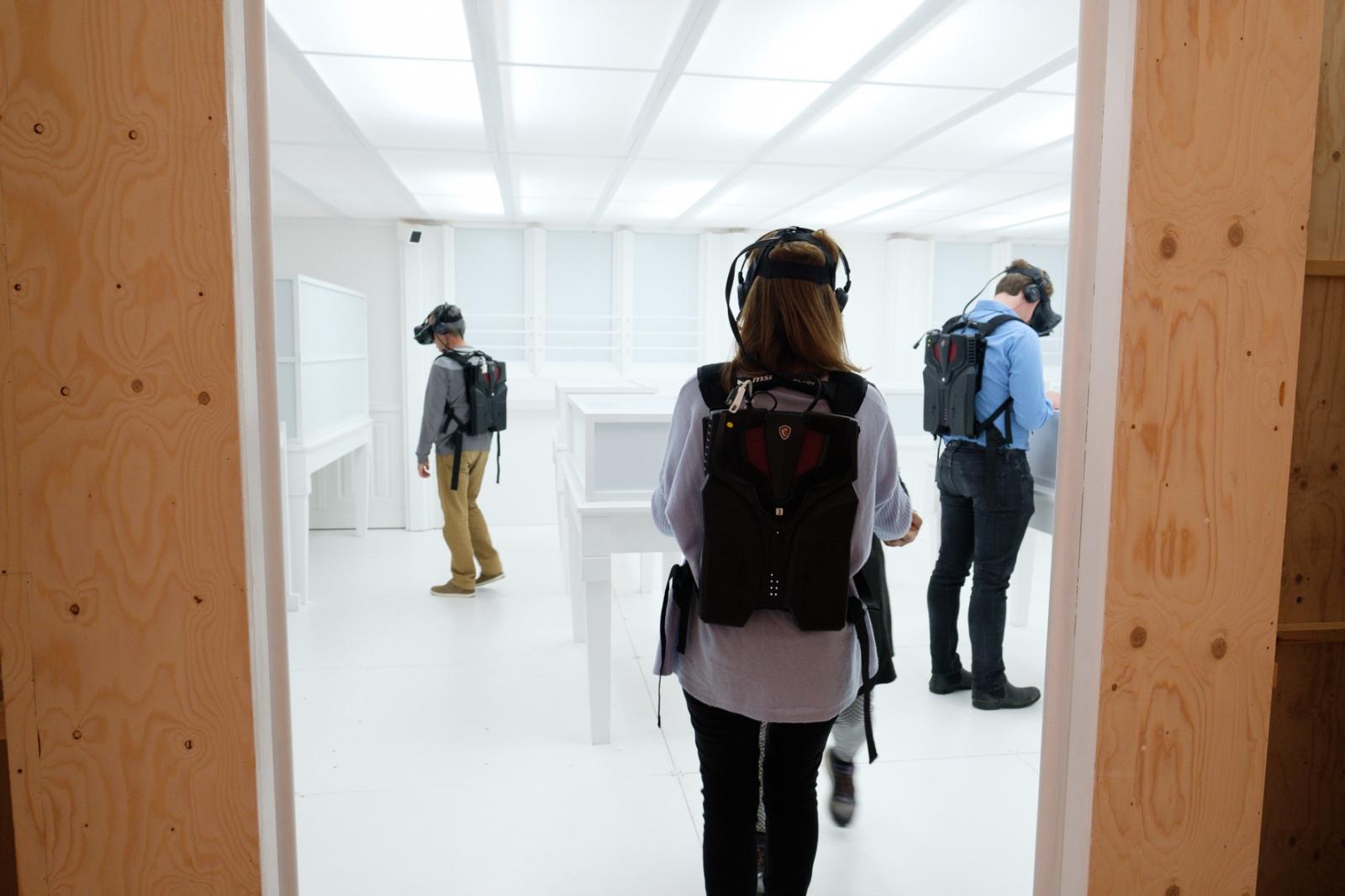 Ausstellungsbesucher mit VR-Brillen vor augenscheinlich leeren Wänden