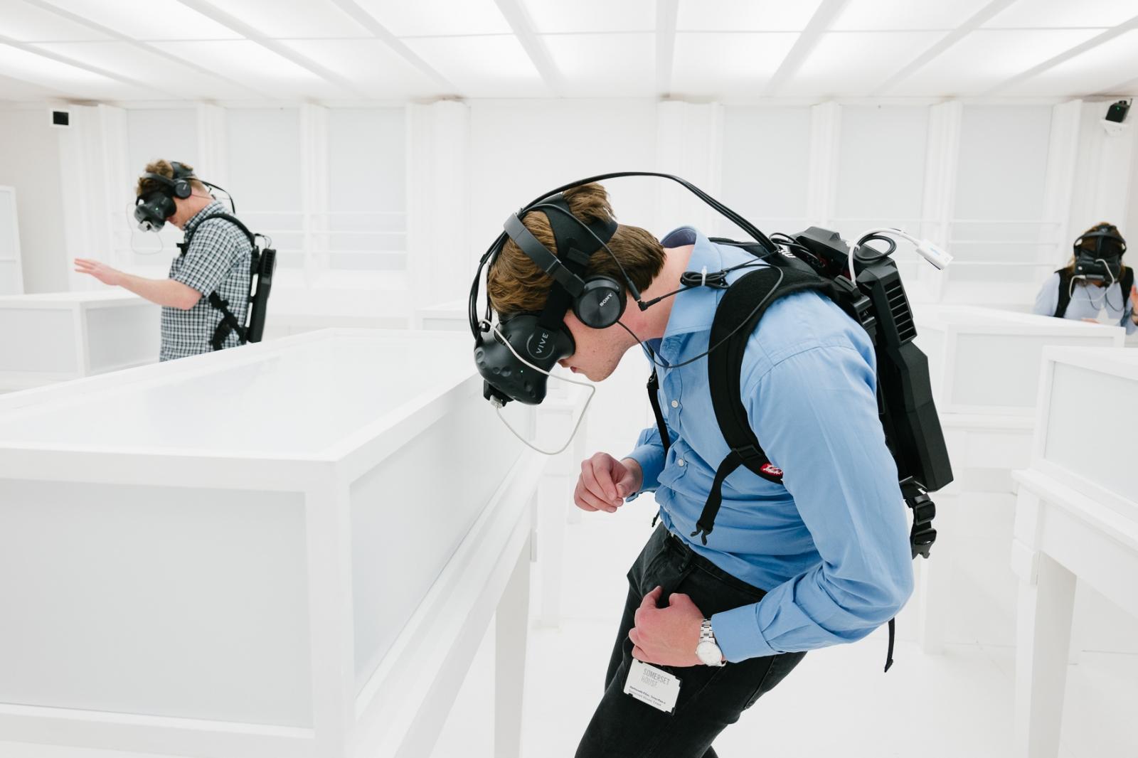 Ausstellungsbesucher mit VR-Brillen vor augenscheinlich leeren Wänden und Vitrinen