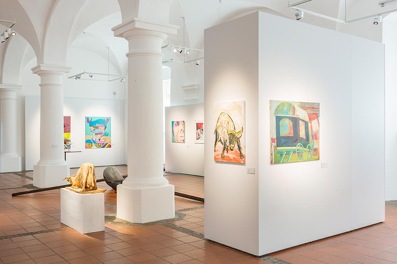 Ausstellungsraum mit Wandmodul und großem Bild, daneben Kinderwagen von Ausstellungsbesuchern