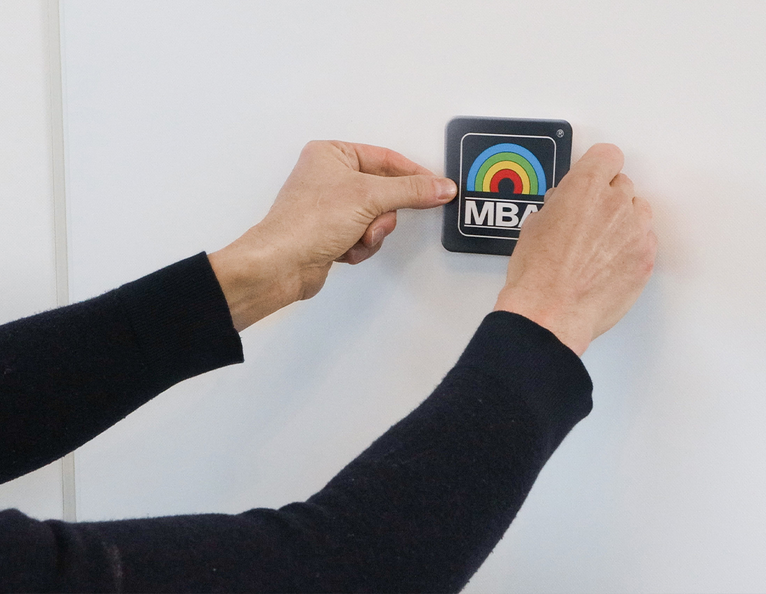 Das MBA-Logo wird auf die Scenario Homeoffice-Kit angebracht.