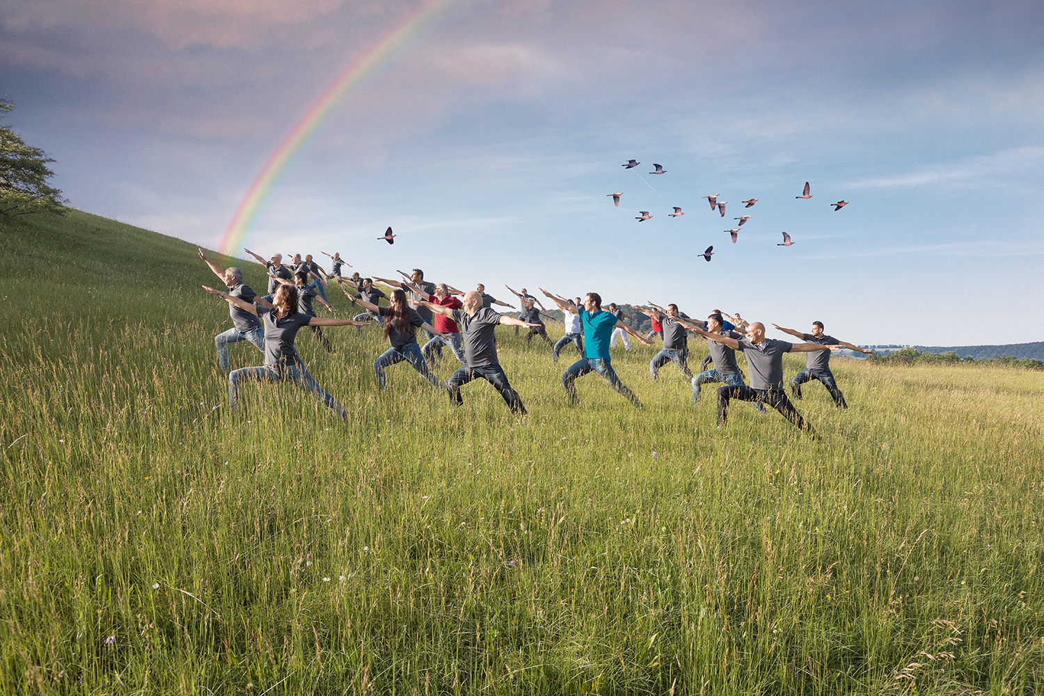 MBA Team in meditativer Pose in der Natur mit Regenbogen